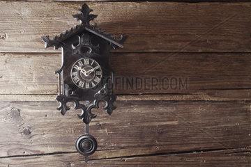 uralte Schwarzwaelder Kuckucksuhr aufgehaengt an einer rustikalen Holzwand