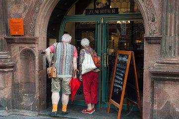 Heidelberg  Deutschland  Touristen studieren Speisekarte eines Restaurants