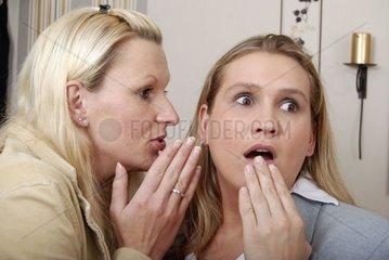 Junge Frauen fluestern