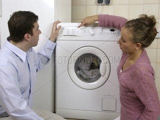Frau zeigt Mann die Bedienung der Waschmaschine