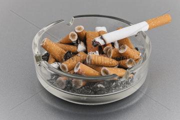 Voller Aschenbecher mit glimmender Zigarette