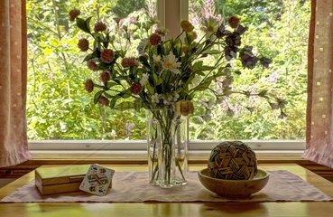 Stillleben mit Kunstblumen und Pikdame vor einem Fenster