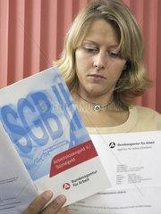 Frau liest Buch der Bundesagentur fuer Arbeit