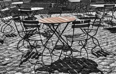 Stuehle und Tische in einem Gartenlokal