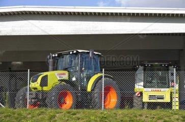 Traktoren und Maehdrescher von Claas hinter der Umzaeunung eines Landmaschinen-Haendlers