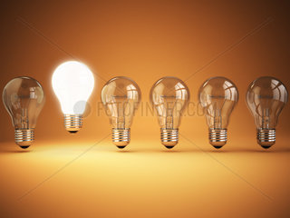 Idea or uniqueness  originality concept. Row of light bulbs with glowing one on orange background