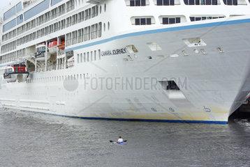 Das Kreuzfahrtschiff Azamara Journey wird von einem einsitzigen Paddelboot passiert  Rostock-Warnemuende  August 2011