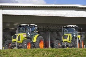 Zwei Traktoren von Claas hinter der Umzaeunung eines Landmaschinen-Haendlers