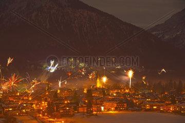Silvesterfeuerwerk ueber Oberstdorf mit hell erleuchteteter Schattenbergschanze  dahinter der Schattenberg  Allgaeuer Alpen  Allgaeu  Bayern  Deutschland  Europa