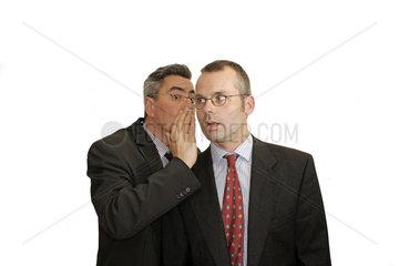 Geschaefsmann fluestert Partner etwas ins Ohr