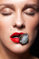 Close up shot of bijouterie ring with stone in female lips
