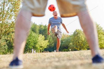 Aktiver Senior beim Fussball im Park