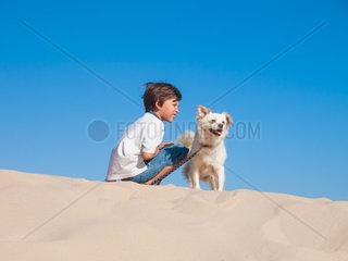 Junge mit seinem Hund auf einer Duene