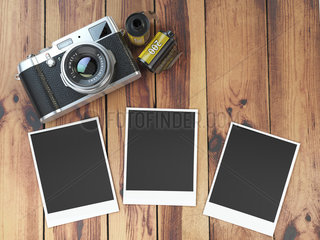 Retro camera  empty photo frames pictures and film canisterrs on wood table.
