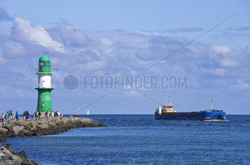 Seefahrer- und Leuchtturmromantik in einem  ein Frachtschiff faehrt durch die Hafeneinfahrt von Rostock-Warnemuende  Deutschland