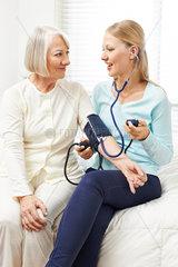Frau macht Blutdruckmessung bei Seniorin