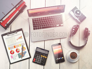 Office workplace. Wooden desk background with laptop  mobile phone  digital camera  calculator  business charts  coffee  binders and loudspeakers. Office workspace.