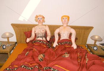 zwei Gummipuppen im Ehebett
