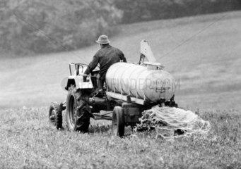 Siebziger Jahre  Landwirtschaft  Duengung  Bauer faehrt mit einem Traktor und Duengewagen ueber einen Acker  Schwarzwald  Baden-Wuerttemberg