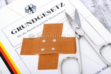 Deutsches Grundgesetz mit Pflaster und Schere  Symbolfoto Beschneidung und deutsches Recht