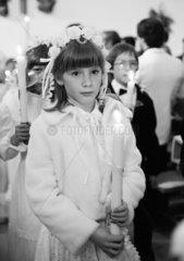 Achtziger Jahre  Religion  Christentum  Erstkommunion  Maedchen und Jungen ziehen in einer Prozession in die Kirche ein und halten Kommunionskerzen in der Hand