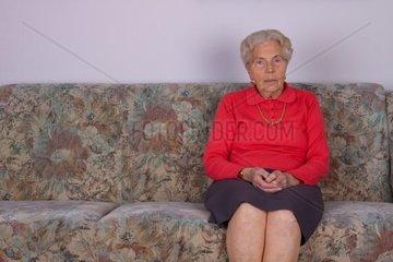 Eine alte Frau sitzt auf Ihrem Sofa