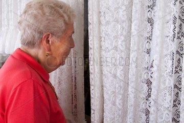 Ein alte Frau blickt aus dem Fenster