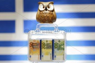 Eule auf Geldkoffer vor Griechenlandfahne  EU-Hilfen fuer Griechenland