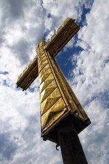 goldfarbenes Kreuz vor bewoelktem Himmel