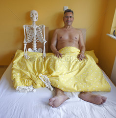 Mann mit Skelett im Bett