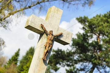 schraeg stehendes Grabkreuz mit Jesusfigur