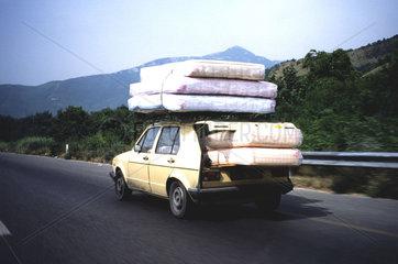 kleines Auto transportiert viele Matrazen