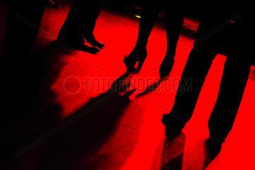 rote Tanzflaeche mit schwarzen Silhouetten der tanzenden Personen