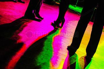Tanzflaeche in grellen Farben mit schwarzen Silhouetten der tanzenden Personen