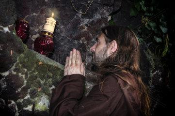ein betender Moench vor einer brennenden Kerze