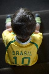 Berlin  Deutschland  ein Junge mit einem Brasilien-Fussballtrikot sitzt auf einer Treppe und schmollt