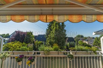 Balkon mit Markise und Balkonblumen an einem Sommertag