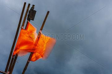 Orangefarbene Fahnen an Bambusstangen wehen vor dunklem Himmel im Wind