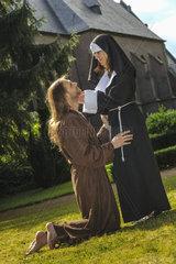 kniender Moench vor einer Nonne