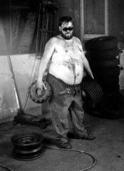 dicker Arbeiter mit Reifen