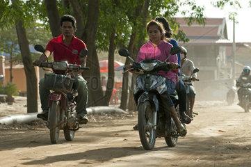 Junge Leute auf Motorraedern auf einer Dorfstrasse im Dorf Areyskat bei Phnom Penh  Kambodscha