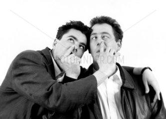 zwei Maenner bohren sich gegenseitig in der Nase