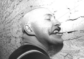 glatzkoepfiger Mann beisst in Nagel an der Wand