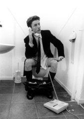 Mann telefoniert auf WC