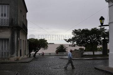 Colonia del Sacramento  Uruguay  Mann ueberquert verregnete Strasse