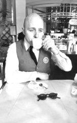 glatzkoepfiger Mann trinkt Kaffee