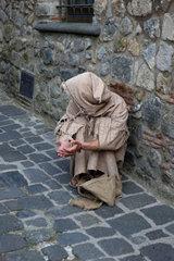 Bolsena  Italien  ein in Lumpen gekleideter Mann bettelt um Almosen