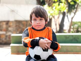 Enttaeuscht guckender Junge mit Fussball im Park