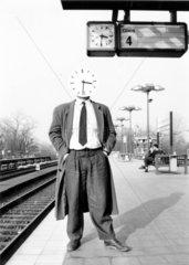 Mann mit Uhr als Kopf auf Bahnsteig