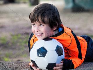 Gluecklicher Junge mit Ball und Torwart Trikaot
